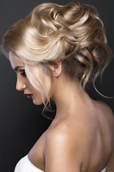 Piękna blond kobieta o doskonałej skórze, wieczorowym makijażu, fryzurze ślubnej