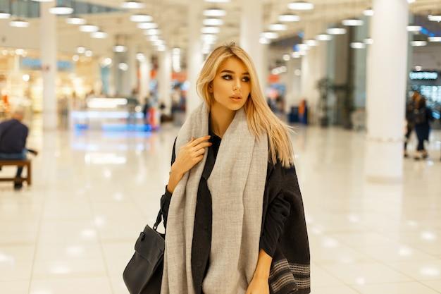 Piękna blond kobieta o ślicznej twarzy w modnym stylowym płaszczu z szalikiem i czarną modną torebką w centrum handlowym