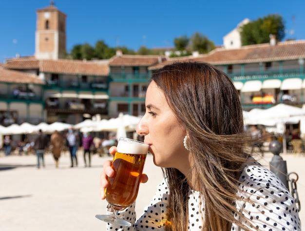 Piękna blond kobieta pije piwo na typowym wiejskim placu