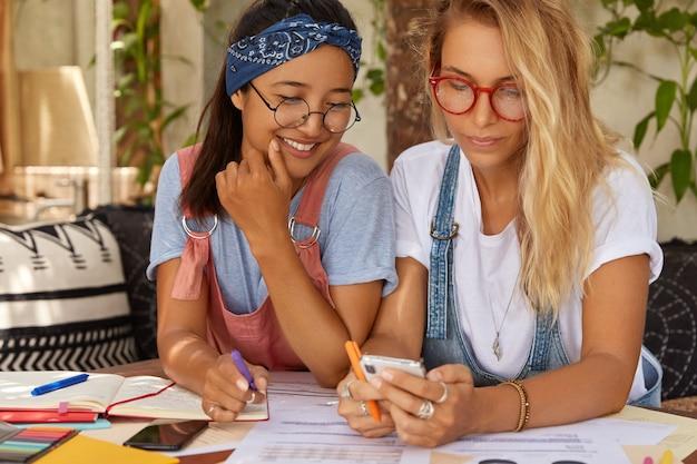 Piękna blond kobieta posiada urządzenie inteligentnego telefonu