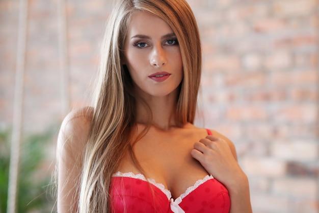 Piękna blond kobieta pozuje w czerwonej bieliźnie