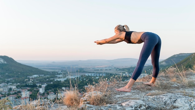 Piękna blond kobieta praktykuje jogę na świeżym powietrzu