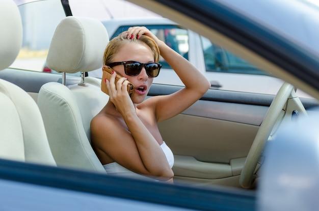 Piękna blond kobieta prowadzi swój kabriolet i rozmawia przez telefon