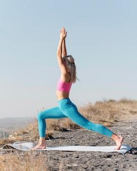 Piękna blond kobieta robi joga na świeżym powietrzu