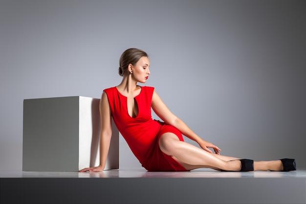 Piękna blond kobieta siedzi w czerwonej sukience przez biały sześcian na szarym tle.