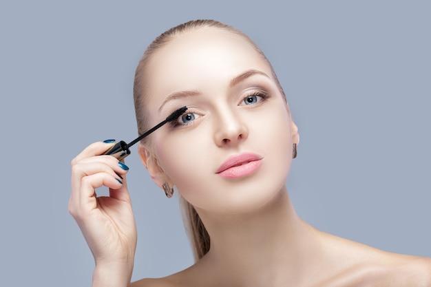 Piękna blond kobieta stosowania makijażu na twarzy na szarym tle. idealny makijaż dla niebieskich oczu. pędzelek do tuszu do rzęs