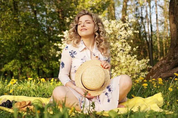 Piękna blond kobieta - szczęśliwy styl życia, weekendowy spacer w parku piknikowym w letnim ogródku, modelka siedzi na kratce z jedzeniem - letnia pogoda