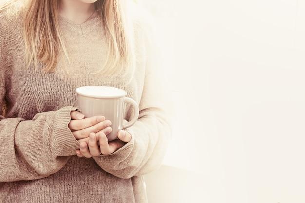 Piękna blond kobieta trzyma dużą filiżankę herbaty i stoi przy oknie.