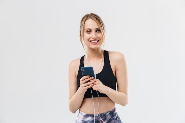 Piękna blond kobieta ubrana w odzież sportową, ćwicząca i słuchająca muzyki ze smartfonem podczas fitness w siłowni na białym tle nad białą ścianą