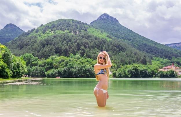 Piękna blond kobieta w białym bikini przy jeziorem