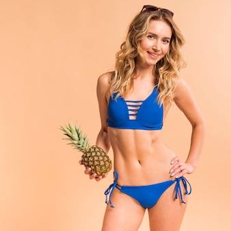 Piękna blond kobieta w błękitnym swimsuit z ananasem