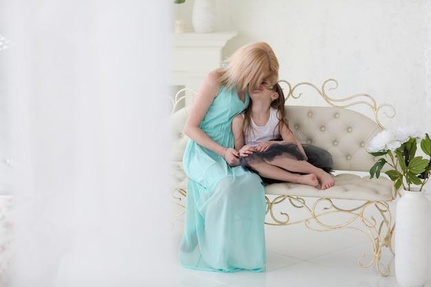 Piękna blond kobieta w granatowej greckiej sukni z córką