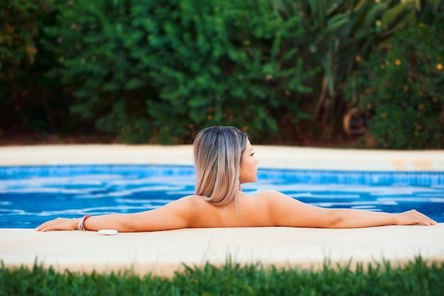 Piękna blond kobieta w luksusowym basenie, relaksujący i luksusowy styl życia. widok z tyłu