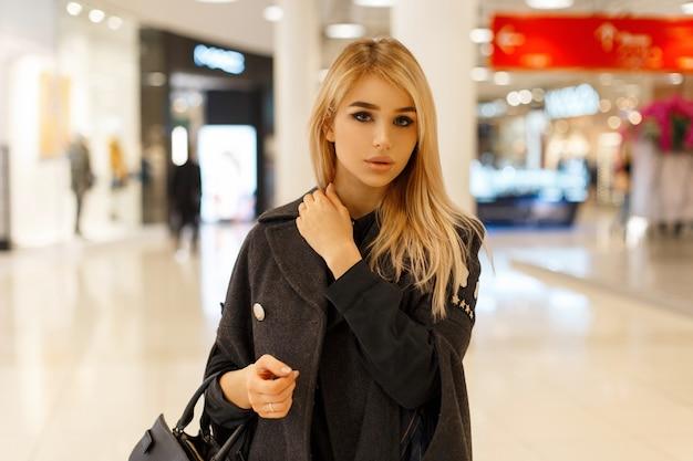 Piękna blond kobieta w modnym płaszczu w centrum handlowym