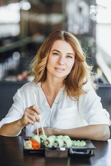 Piękna blond kobieta w średnim wieku jedząca rolę kalifornii w japońskiej restauracji na letnim tarasie