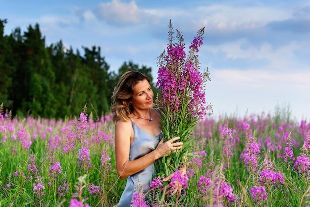 Piękna blond kobieta w szarej sukience relaksuje się bukiet kwiatów na łące fireweed