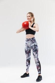 Piękna blond kobieta w wieku 20 lat ubrana w odzież sportową ćwiczącą i wykonującą ćwiczenia z piłką fitness podczas aerobiku na białym tle nad białą ścianą