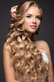 Piękna blond kobieta w wizerunku panny młodej z kwiatami. piękna twarz i fryzura