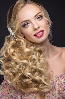 Piękna blond kobieta w wizerunku panny młodej z purpurowymi kwiatami na jej głowie