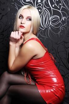 Piękna blond kobieta z czerwoną sukienką. fotografia mody