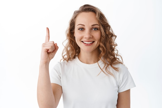 Piękna blond kobieta z kędzierzawą fryzurą, wskazującym palcem w górę i uśmiechnięta, pokazująca reklamę, stojąca nad białą ścianą