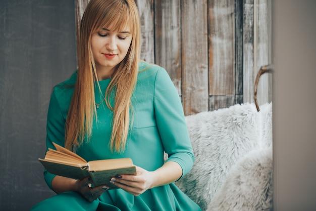 Piękna blond kobieta z książką w ona ręki