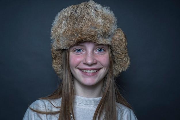 Piękna blond młoda dziewczyna w zimowym futrzanym kapeluszu w pomieszczeniu na czarnym tle, portret z bliska