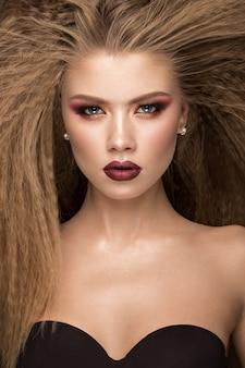 Piękna blond modelka: loki, jasny makijaż i czerwone usta. the
