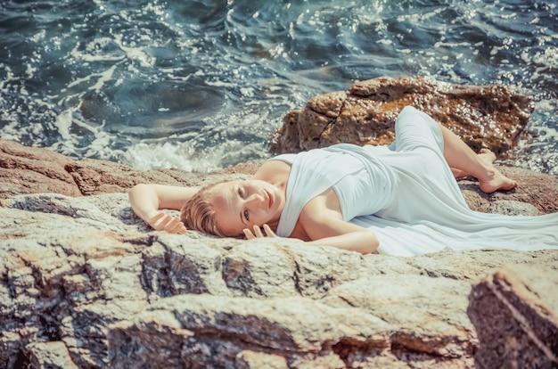 Piękna blond panna młoda w białej ślubnej sukni stojaku na dennym brzeg. tropikalne morze i skały w tle. koncepcja letnich wakacji.