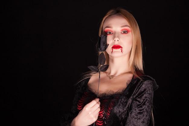 Piękna blond wampirzyca z różą na czarnym tle na halloween.