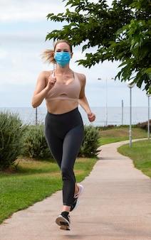 Piękna blondynka biegnie w parku w masce medycznej