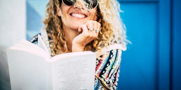 Piękna blondynka czyta książkę papierową usiąść na ziemi przed domem - niebieskie tło drzwi i ściany - dorośli ludzie studiujący lub czytający powieść