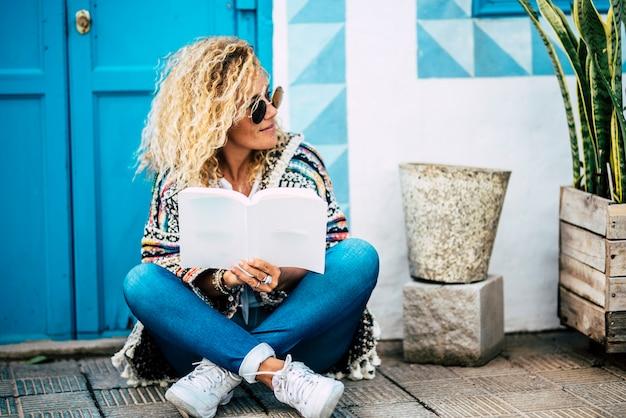 Piękna blondynka czyta papierową książkę, usiądź na ziemi przed domem