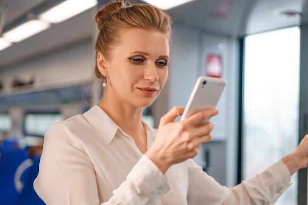 Piękna blondynka jeździ pociągiem, trzymając w rękach telefon