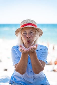 Piękna blondynka kaukaski kobieta w słomkowym kapeluszu i koszuli w paski, dmuchanie pocałunek, siedząc nad morzem w lecie