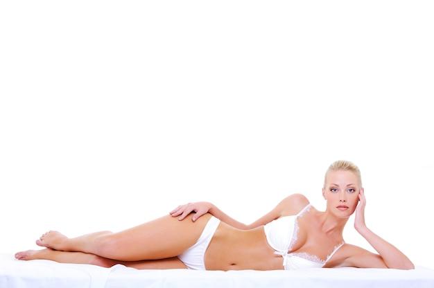 Piękna blondynka kaukaski kobieta z idealnym seksownym ciałem, leżąc na łóżku