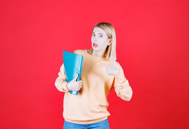 Piękna blondynka kobiet w dżinsach wskazuje niebieski plik, który trzyma prawą ręką