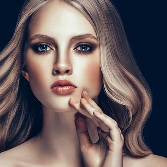 Piękna blondynka kobieta model piękna dziewczyna z doskonały makijaż i fryzurę na czarnym tle.