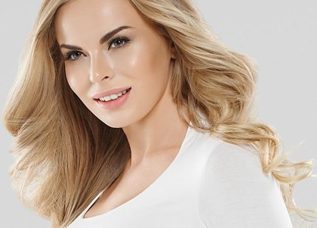 Piękna blondynka kobieta pielęgnacji skóry i urody fryzurę portret koncepcja z długie blond platynowe włosy kręcone na szarym tle. strzał studio.