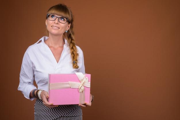 Piękna blondynka kobieta z plecionymi włosami, trzymając pudełko