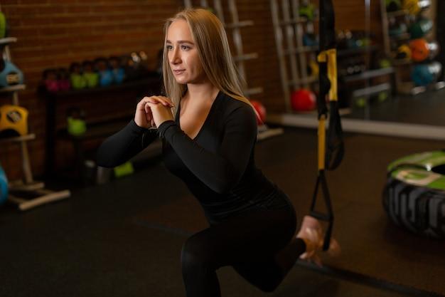 Piękna blondynka lekkoatletka patrzy w przyszłość i robi ćwiczenia rzuca się naprzód na siłowni.