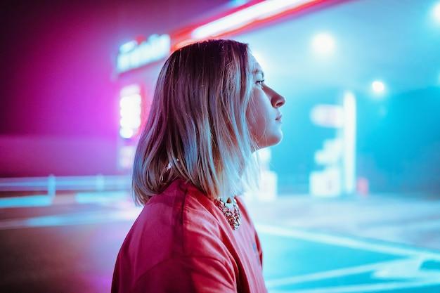 Piękna blondynka lesbijek na stacji benzynowej w nocy w różowym i niebieskim świetle. zdjęcie wysokiej jakości