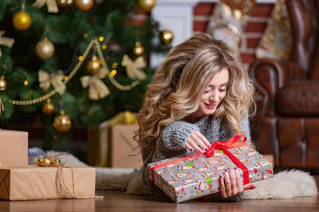 Piękna blondynka leży na ciepłym dywanie i patrzy na jasny świąteczny prezent z czerwoną wstążką w pobliżu choinki
