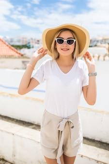 Piękna blondynka młoda kobieta na sobie kapelusz i okulary przeciwsłoneczne, chodzenie po ulicy