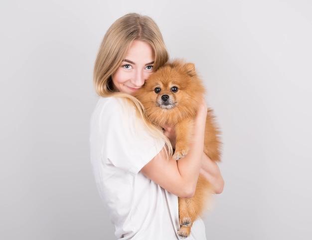 Piękna blondynka młoda kobieta przytula i całuje szczeniaka szpic. miłość między psem a właścicielem. na białym tle na szarym tle.