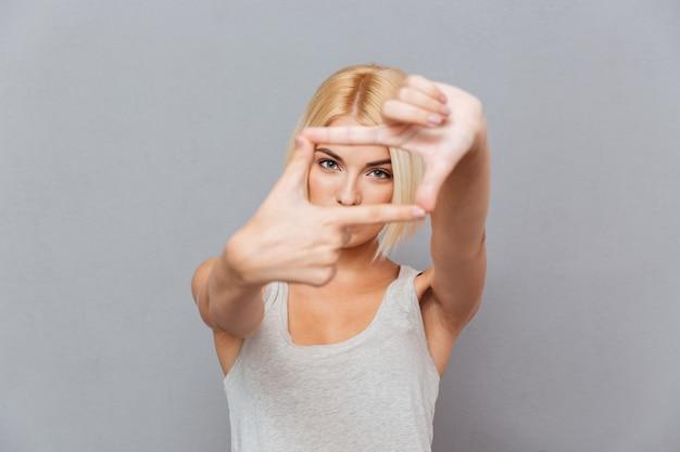 Piękna blondynka młoda kobieta robi ramce palcami nad szarą ścianą