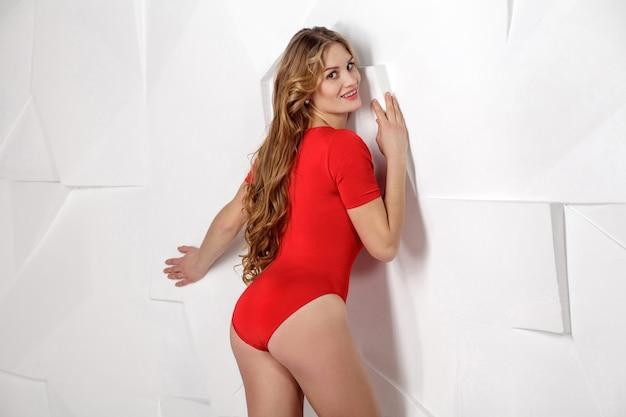 Piękna blondynka młoda kobieta w czerwonym ciele na szarym tle pozowanie