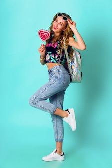 Piękna blondynka moda model dziewczyna trzymając kolorowy różowy pączek. zabawna radosna kobieta ze słodyczami, deser. dieta, koncepcja diety. niezdrowe jedzenie. żywe kolory.