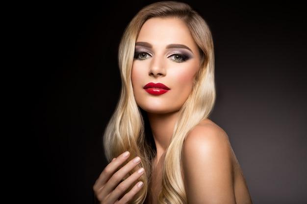 Piękna blondynka model dziewczyny z długimi kręconymi włosami. faliste loki fryzury. czerwone usta.