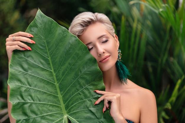 Piękna blondynka model z zamkniętymi oczami. naturalny makijaż i zielone liście
